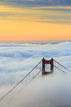 CLKFV42925 Golden Gate Bridge emerging from the morning fog at sunrise. San Francisco, Marin County, California, USA.
