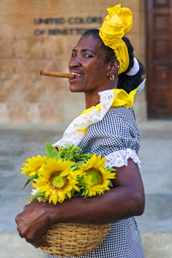 CUB1420 Cuba, Havana, Habana Vieja.  A woman flower seller in Habana Vieja with a large cigar.