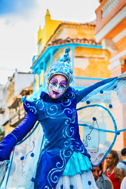 CUB1430 Cuba, Havana, Habana Vieja.  A colourful stilt walker pauses to entertain passers-by in a street in Habana Vieja.