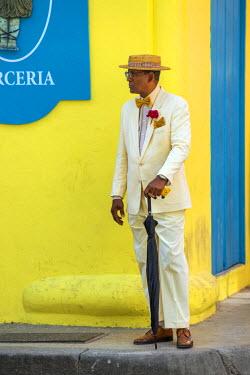 CUB1456 Cuba, Havana, Plaza de Armas, Habana Vieja, Old Havana. A Cuban dandy stands at a street corner, cigar in hand.