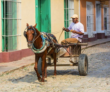 CUB1531 Cuba, Sancti Spiritus Province, Trinidad.  A man drives his horse-drawn cart down a cobblestone street.