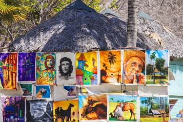 CB02489 Cuba, Jardines del Rey, Cayo Guillermo, Playa El Paso, Paintings for sale outside thatched hut at Melia Hotel