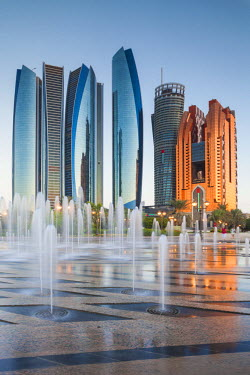 UE02357 UAE, Abu Dhabi, Etihad Towers and Emirates Palace Hotel fountains, dusk