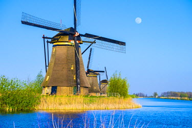 NLD0087AW Netherlands, South Holland, Kinderdijk, UNESCO World Heritage Site. The moon rises above historic Dutch windmills on the polders.