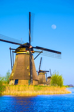 NLD0088AW Netherlands, South Holland, Kinderdijk, UNESCO World Heritage Site. The moon rises above historic Dutch windmills on the polders.