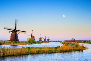 NLD0092AW Netherlands, South Holland, Kinderdijk, UNESCO World Heritage Site. The moon rises above historic Dutch windmills on the polders at sunset.