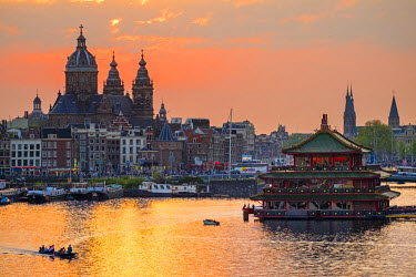 NLD0218AW Netherlands, North Holland, Amsterdam. City skyline at sunset with domes of Basilica of Saint Nicholas.