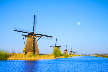 NLD0236AWRF Netherlands, South Holland, Kinderdijk, UNESCO World Heritage Site. The moon rises above historic Dutch windmills on the polders.
