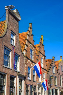 NLD0266AWRF Netherlands, North Holland, Edam. Brick houses with Dutch flags hanging outside for national holiday.