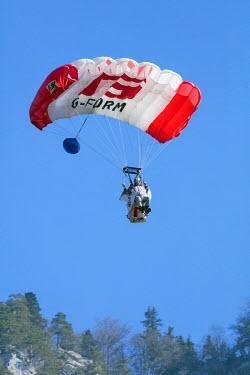 FRA9275 Europe, France, Haute Savoie, Rhone Alps, Chamonix, wingsuit base jumper landing with parachute