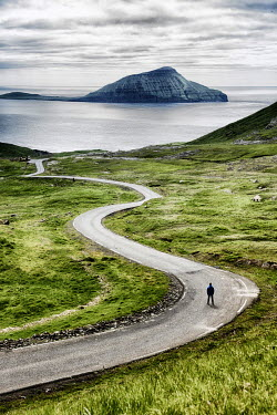 DEN0284AW Stremnoy island, Faroe Islands, Denmark. Man standing on a bending road. (MR)