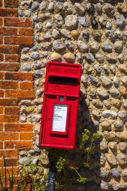UK479RF UK, England, Norfolk, North Norfolk, Blakeney, Red Post Box against traditional flint wall