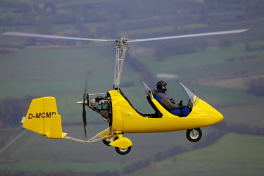 IBLBLO01763997 Aerial view of yellow gyrocopter, helicopter over the Muensterland area, North Rhine-Westphalia, Germany
