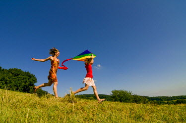 IBLDJS01642472 Woman and girl running with a kite in a meadow in the Black Forest, Baden-Wuerttemburg, Germany