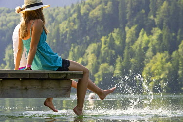 IBLDJS02039780 Young women sitting on a landing stage on Lake Schwansee near Fuessen, Allgaeu region, Bavaria, Germany