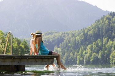 IBLDJS02039783 Young women sitting on a landing stage on Lake Schwansee near Fuessen, Allgaeu region, Bavaria, Germany