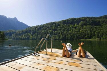 IBLDJS02039784 Young women lying on a landing stage on Lake Schwansee near Fuessen, Allgaeu region, Bavaria, Germany
