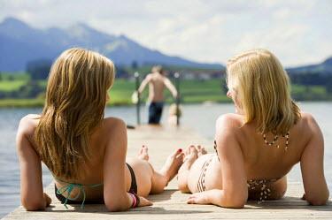 IBLDJS02043693 Two women in bikinis on a jetty, Lake Hopfensee near Fuessen, Allgaeu, Bavaria, Germany