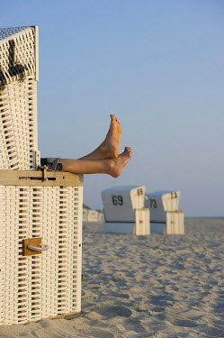IBLDJS02052876 Roofed wicker beach chair and bare feet, Westerland, Sylt island, Schleswig-Holstein, Germany