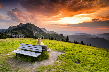 IBLGZS02235160 Woman sitting on a wooden bench enjoying the views from the summit of Mt Bauneck, Bavaria, Germany