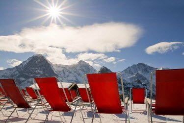 IBLDJS01142677 Red deck chairs with sun, in the back the Bernese Oberland, Grindelwald, Canton Bern, Switzerland