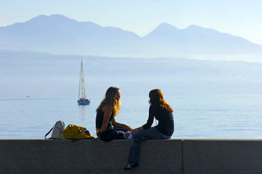 IBLGUF00144900 Young women chatting on a wall at Lake Geneva, Lac Leman, Ouchy, Lausanne, Switzerland