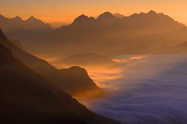 IBLSEI01771029 Mountain valley under fog with mountain peaks in the evening light, Allgaeu Alps, Kleinwalsertal valley, Vorarlberg, Austria