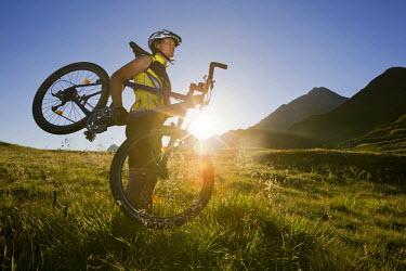IBLVCH01124997 Mountain biker carrying his bike, Zillertal Alps, Mayerhofen, North Tyrol, Austria