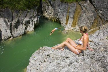 IBLVCH01145902 Young woman watching a cliff diver, Brandenberger Ache River, North Tyrol, Austria