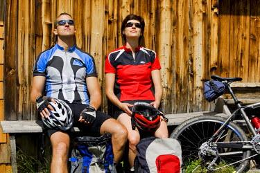 IBLVCH01146022 Mountain bikers taking a break in front of a hut, Alpbachtal, North Tyrol, Austria