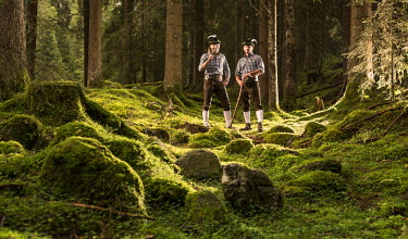 IBLVCH03732216 Woodcutters standing in a forest, Alpbach, Tyrol, Austria