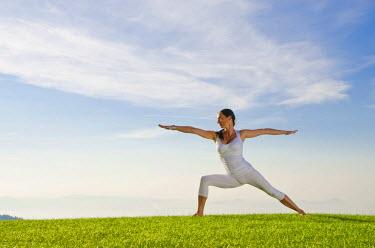 IBLFBD02045298 Young woman practising Hatha yoga outdoors, showing the pose virabhadrasana II, proud warrior, Nove Mesto, Okres Teplice, Czech Republic