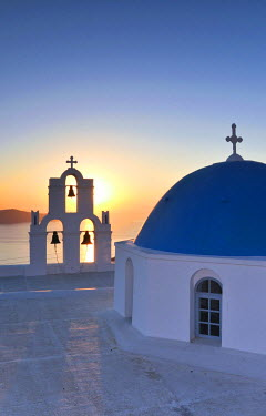 IBLGZS00903373 White Greek church with a blue dome and a bell tower at sunset, Firostefani, Santorini, Cyclades, Greece