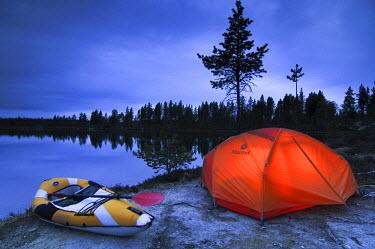 IBLGZS00295225 Illuminated tent and canoe at dawn, Femund, Femundsmarka national park, Norway
