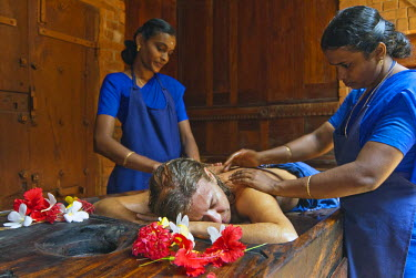 IBLOMK01939216 Woman receiving Ayurvedic massage from staff, Ayurvedic Health Resort Somatheeram, Chowara, Malabar Coast, South India, India