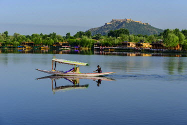 IBLFBD03713907 A shikara boat crossing Dal Lake, houseboats and the Durrani Fort on Hari Parbat hill at the back, Srinagar, Jammu and Kashmir, India