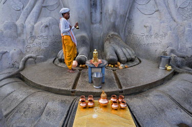 IBLOMK01902107 Priest in front of the Jain statue of Gomateshwara, Indragiri Hill, Sravanabelagola, Hassan district, Karnataka, South India, India