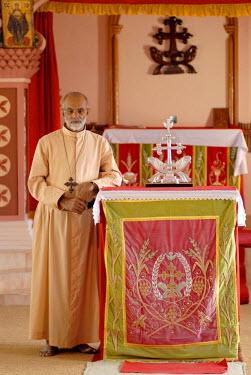 IBLOMK02059294 Catholic priest in front of the cross of the St. Thomas Christians, Mar Thoma Sleeha monastery, Thiruvalla, Kerala, South India, India