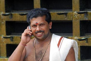IBLOMK02060375 Hindu priest talking on a mobile phone, temple of Ettumanur, Kerala, South India, India