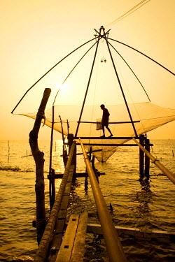 IBLOMK03618915 Fisherman holding a landing net in a Chinese fishing net at sunrise, Vembanad lake, Kerala, India