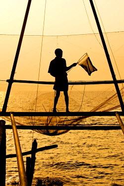 IBLOMK03618948 Fisherman holding a landing net in front of a Chinese fishing net at sunrise, Vembanad lake, Kerala, India