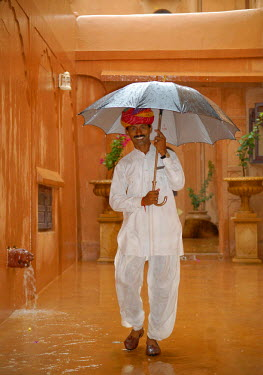 IBLOMK01933335 Servant with an umbrella during a monsoon rain, Khimsar Fort Heritage Hotel, Rajasthan, northern India