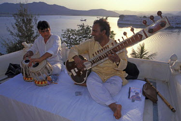 IBLOMK02068886 Musicians with a tabla and a sitar, playing music in front of the Taj Lake Palace Hotel, Lake Piccola, Udaipur, Rajasthan, northern India, India