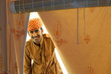 IBLOMK02069135 Friendly employee, tent entrance, Royal Jodhpur Camp, Mool Sagar, heritage hotel and pleasure gardens of the Maharajas of Jodhpur, Jaisalmer, Thar Desert, Rajasthan, North India, India