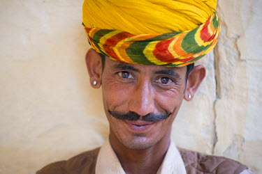 Servant wearing a yellow turban and earrings, portrait, Mehrangarh Fort, Jodhpur, Rajasthan, India