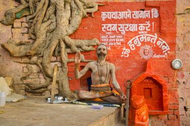 IBLFBD02163020 Sadhu, holy man, sitting, greeting at the ghats of Varanasi, Uttar Pradesh, India