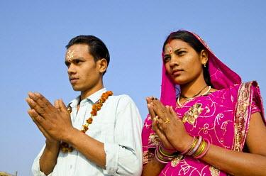 IBLFBD02163089 Pilgrims praying at Sangam, the confluence of the holy rivers Ganges, Yamuna and Saraswati, in Allahabad, Uttar Pradesh, India
