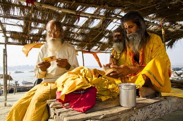 IBLFBD02163111 Sadhus reciting from the holy books in the morning, at Sangam, the confluence of the holy rivers Ganges, Yamuna and Saraswati, in Allahabad, Uttar Pradesh, India