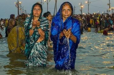 IBLFBD03151784 Women taking a bath in the Sangam, the confluence of the rivers Ganges, Yamuna and Saraswati, in the early morning, Kumbha Mela mass Hindu pilgrimage, Allahabad, Uttar Pradesh, India