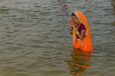 IBLFBD03151798 Woman wearing an orange sari taking a bath in the Sangam, the confluence of the rivers Ganges, Yamuna and Saraswati, in the early morning, Kumbha Mela mass Hindu pilgrimage, Allahabad, Uttar Pradesh,...